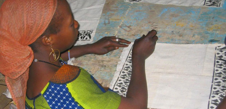 Malisk kvinne jobber med <strong>tekstil</strong>